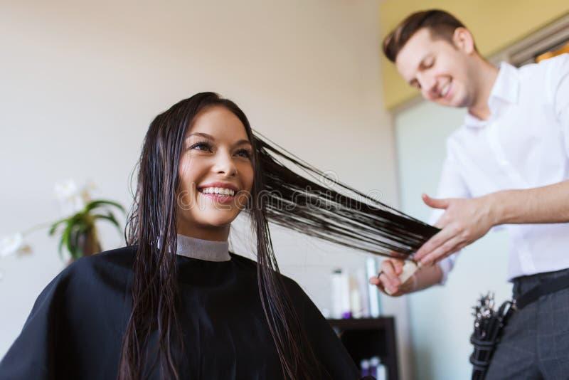 Szczęśliwa kobieta z stylisty tnącym włosy przy salonem obraz royalty free