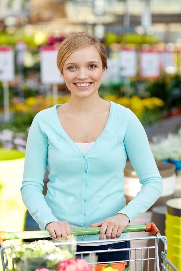 Szczęśliwa kobieta z wózek na zakupy i kwiatami w sklepie zdjęcia stock
