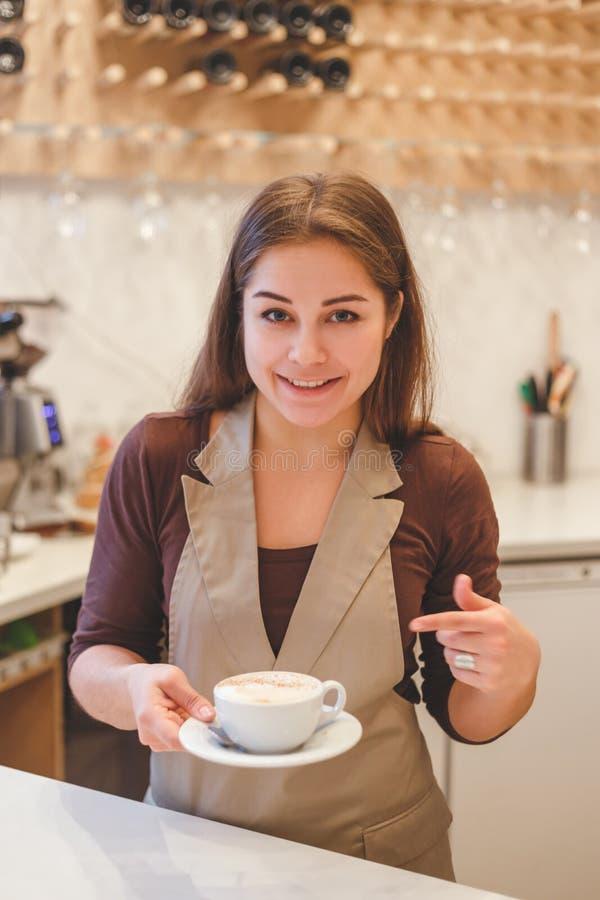 Szczęśliwa kobiety barista ofiary kawa klient przy kawiarnią obrazy stock