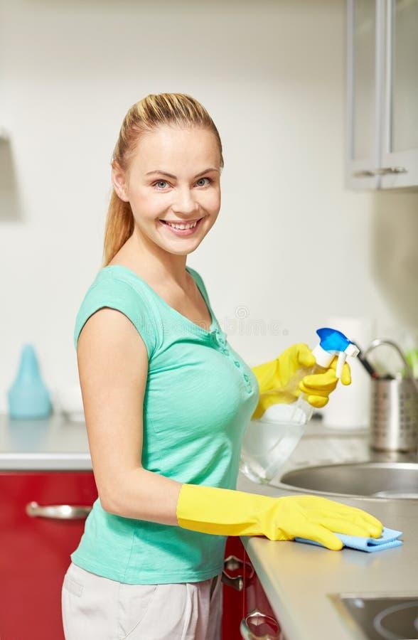 Szczęśliwa kobiety cleaning stołu kuchnia w domu obraz stock