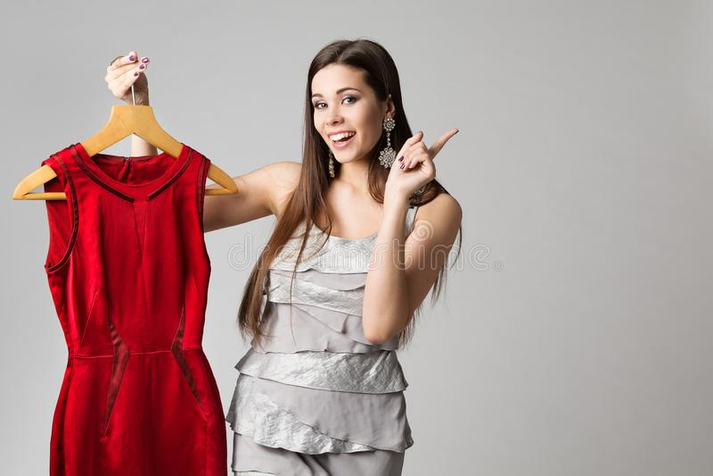 Szczęśliwa kobiety mienia rewolucjonistki suknia na wieszaku, moda modela ubraniach i Wskazywać na bielu, zdjęcia stock