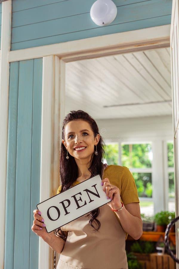 Szczęśliwa kobiety pozycja na ganeczku jej sklep obraz stock