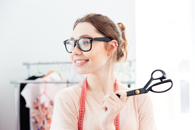 Szczęśliwa kobiety szwaczka uśmiecha się nożyce w projekta studiu i trzyma fotografia stock