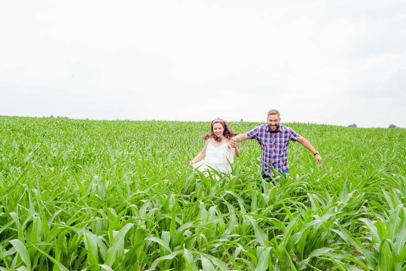 Szczęśliwa kochająca młoda dorosła para wydaje czas na polu na słonecznym dniu obrazy royalty free