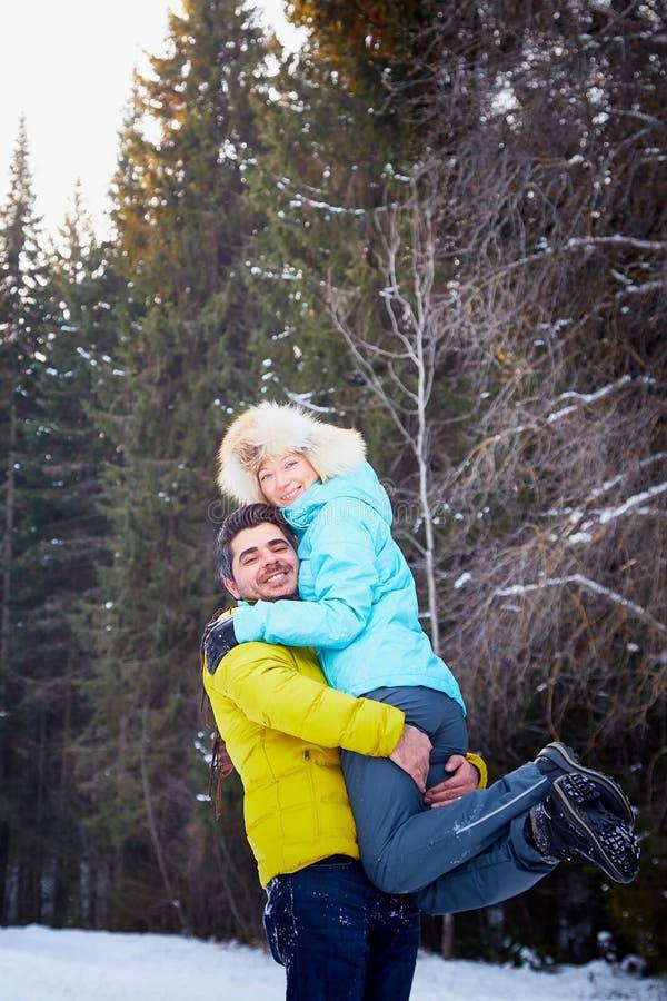 Szczęśliwa kochająca para w śnieżnej zimy lasowej Zwyczajnej Rosyjskiej dziewczynie i przystojnym tureckim mężczyźnie ma zabawę i obraz stock