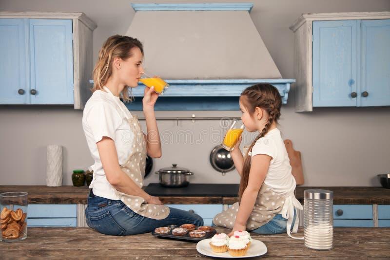 Szczęśliwa kochająca rodzina w kuchni Matki i dziecka córki dziewczyna je ciastka robili z pomarańcze zdjęcie royalty free