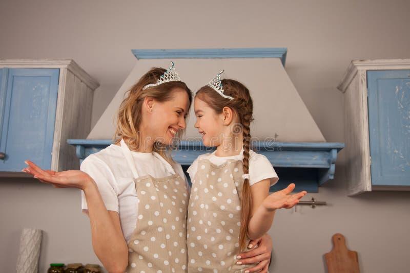 Szczęśliwa kochająca rodzina w kuchni Matki i dziecka córki dziewczyna jest ubranym korony ma zabawę, patrzeje each inny zdjęcie royalty free