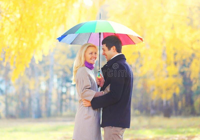 Szczęśliwa kochająca uśmiechnięta para z kolorowym parasolem w ciepły pogodnym obraz stock