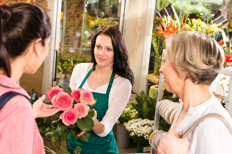 Szczęśliwa kwiaciarni kobieta pokazuje różom kwiatów klientów zdjęcia royalty free