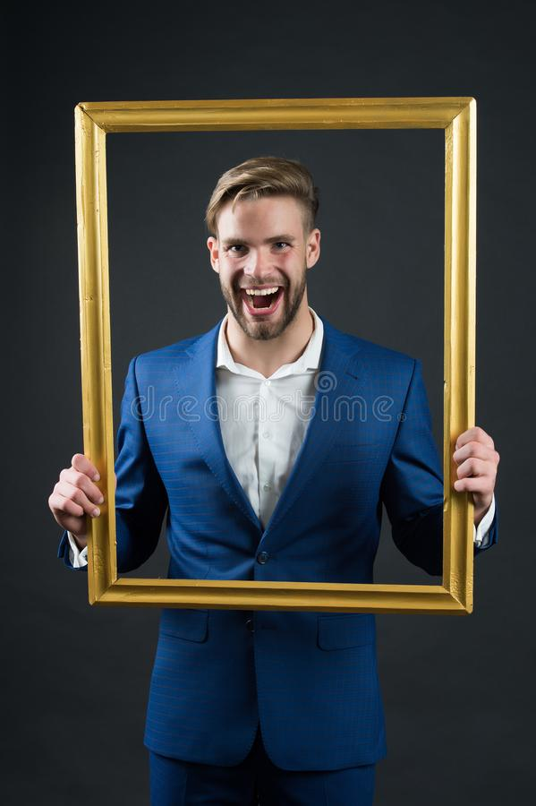 Szczęśliwa mężczyzna chwyta obrazka rama Biznesmena uśmiech przez ramy skupia się mnie Portret ja kamery 3 kanapy dziewczyn na po obrazy stock