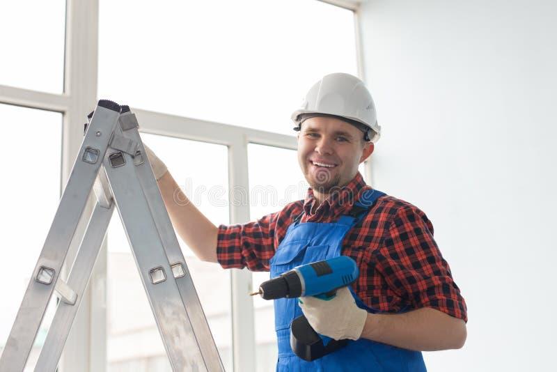 Szczęśliwa męska budowniczy pozycja na drabinie z śrubokrętem przed okno zdjęcie stock