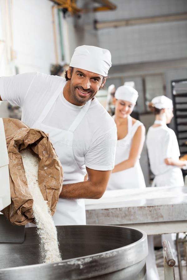 Szczęśliwa Męska Piekarniana dolewanie mąka W Ugniatać maszynę zdjęcia stock