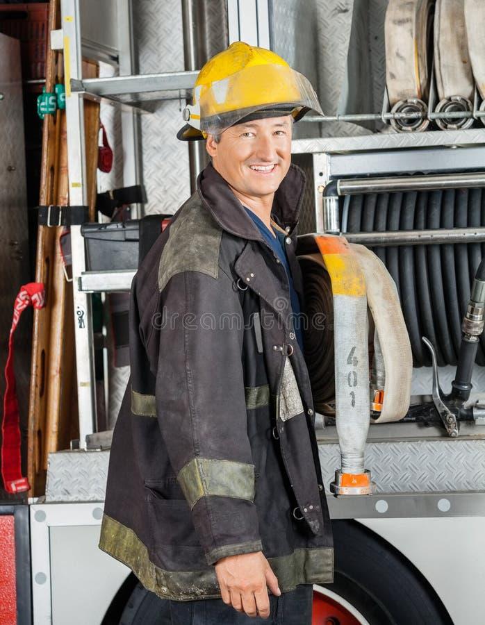 Szczęśliwa Męska strażak pozycja ciężarówką zdjęcia royalty free