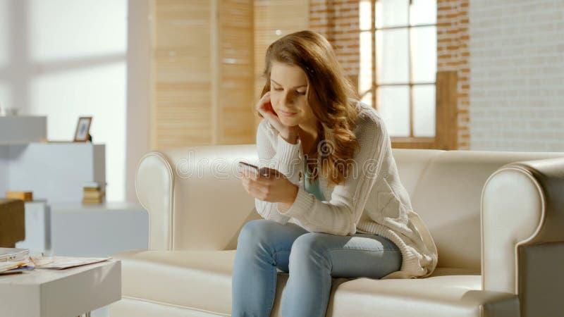 Szczęśliwa młoda żeńska używa wisząca ozdoba app na smartphone, technologia komunikacyjna zdjęcie royalty free