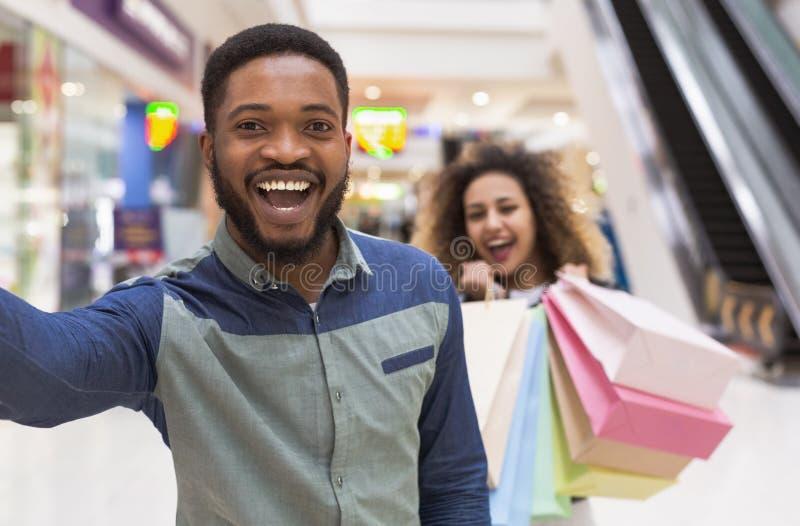 Szczęśliwa młoda afrykańska para ma zabawę wpólnie podczas gdy robiący zakupy zdjęcia royalty free