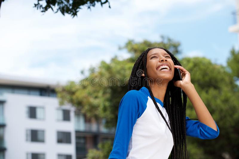 Szczęśliwa młoda amerykanin afrykańskiego pochodzenia dziewczyna opowiada na telefonie komórkowym outdoors fotografia stock