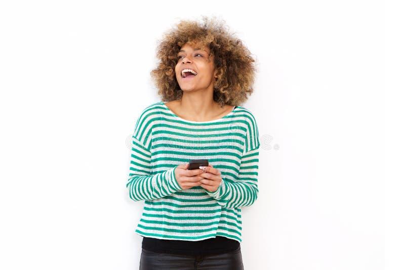 Szczęśliwa młoda amerykanin afrykańskiego pochodzenia kobieta śmia się z telefonu komórkowego abasing białym tłem fotografia royalty free
