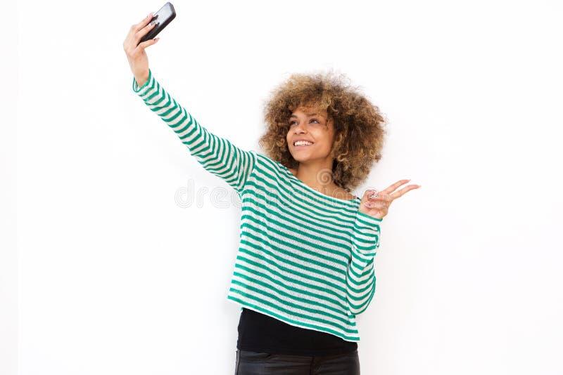 Szczęśliwa młoda amerykanin afrykańskiego pochodzenia kobieta bierze selfie z telefonem komórkowym zdjęcia royalty free