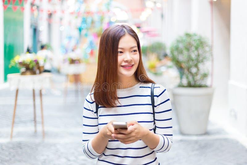 Szczęśliwa młoda atrakcyjna azjatykcia kobieta w przypadkowych ubraniach używać jej s obraz stock
