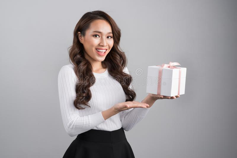 Szczęśliwa młoda azjatykcia kobieta daje prezenta pudełku nad szarym tłem obraz royalty free