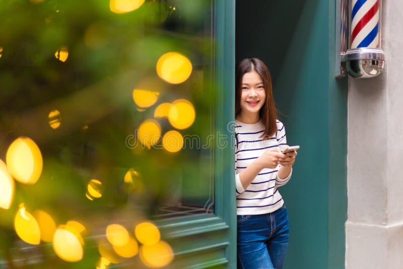 Szczęśliwa młoda azjatykcia kobieta stoi przed a w przypadkowych ubraniach zdjęcia royalty free