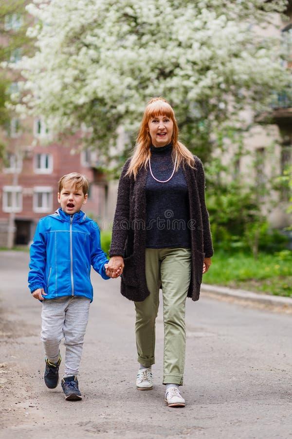 Szczęśliwa młoda babcia i siedem roczniaka chłopiec iść wpólnie ręka w rękę w wiośnie obrazy stock