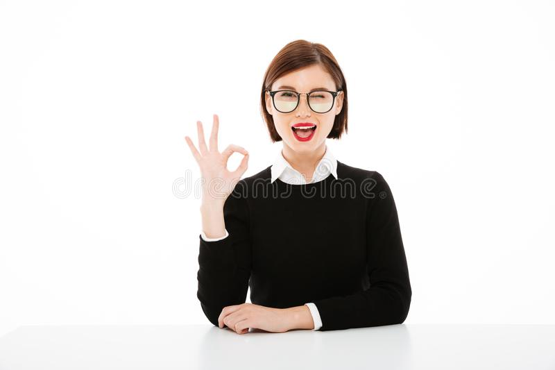 Szczęśliwa młoda biznesowa dama jest ubranym szkła pokazuje zadowalającego gest zdjęcia stock