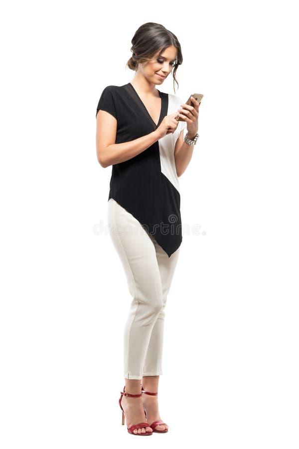 Szczęśliwa młoda biznesowa kobieta relaksuje i pisać na maszynie na telefonie komórkowym w formalnym kostiumu obraz royalty free
