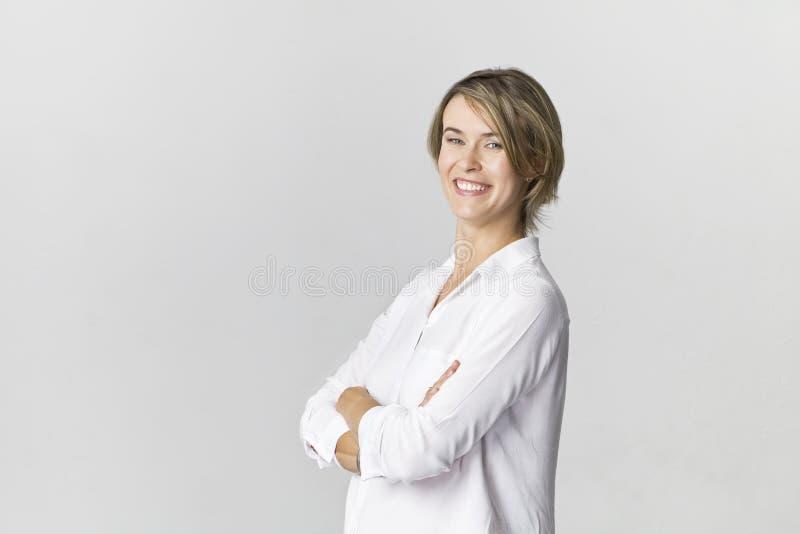 Szczęśliwa młoda blondynki kobieta jest ubranym białego koszulowego uśmiechniętego portret ag zdjęcie stock
