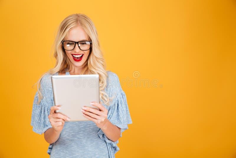 Szczęśliwa młoda blondynki kobieta używa pastylka komputer fotografia royalty free