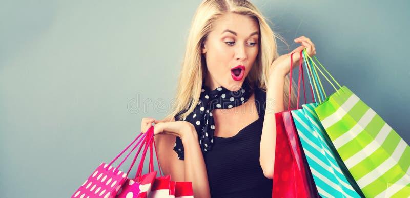 Szczęśliwa młoda blondynki kobieta z torba na zakupy zdjęcie royalty free