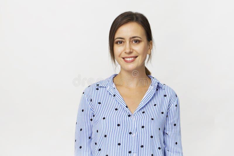 Szczęśliwa młoda brunetki kobieta jest ubranym błękitnego koszulowego uśmiechniętego portret a zdjęcia stock