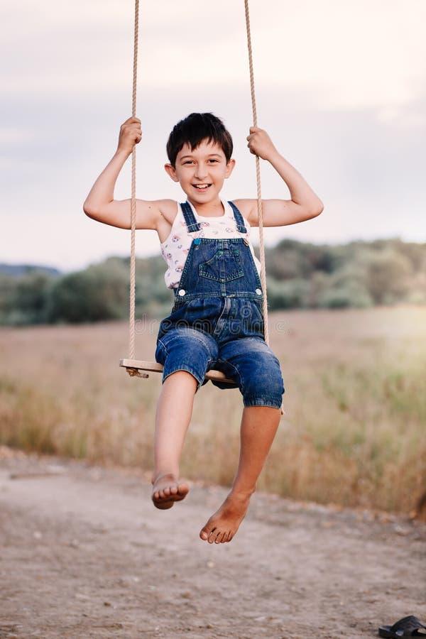 Szczęśliwa młoda chłopiec bawić się na huśtawce w parku zdjęcie royalty free