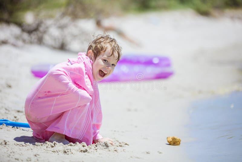 Szczęśliwa młoda chłopiec bawić się z piaskiem na plaży fotografia royalty free