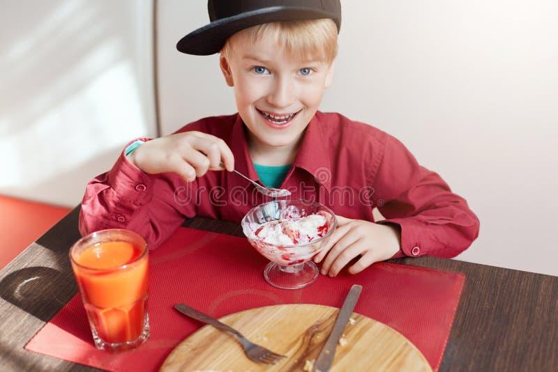 Szczęśliwa młoda chłopiec jest usytuowanym przy cosy caffe je wyśmienicie lód z niebieskimi oczami i blondynem ubierał w czerwone zdjęcie royalty free