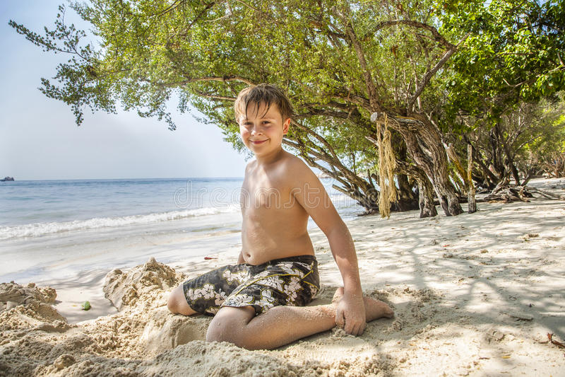 Szczęśliwa młoda chłopiec kopie w piasku plaża zdjęcie royalty free