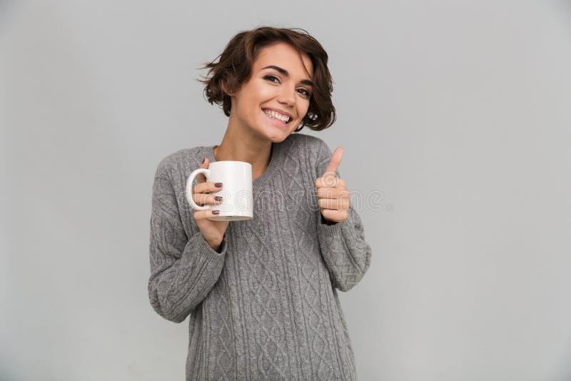 Szczęśliwa młoda dama pije herbaty pokazuje aprobata gest fotografia royalty free