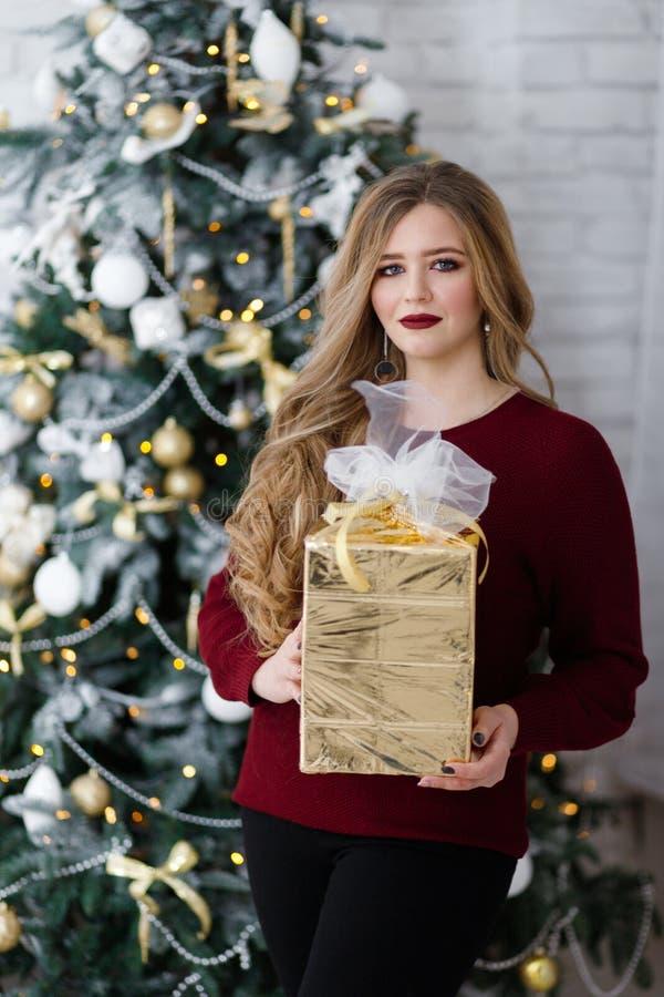 Szczęśliwa młoda dama z długie włosy prezentami grabą blisko choinki zdjęcia stock