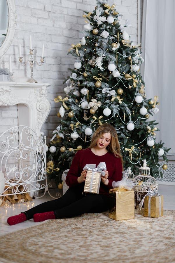 Szczęśliwa młoda dama z długie włosy prezentami grabą blisko choinki fotografia stock