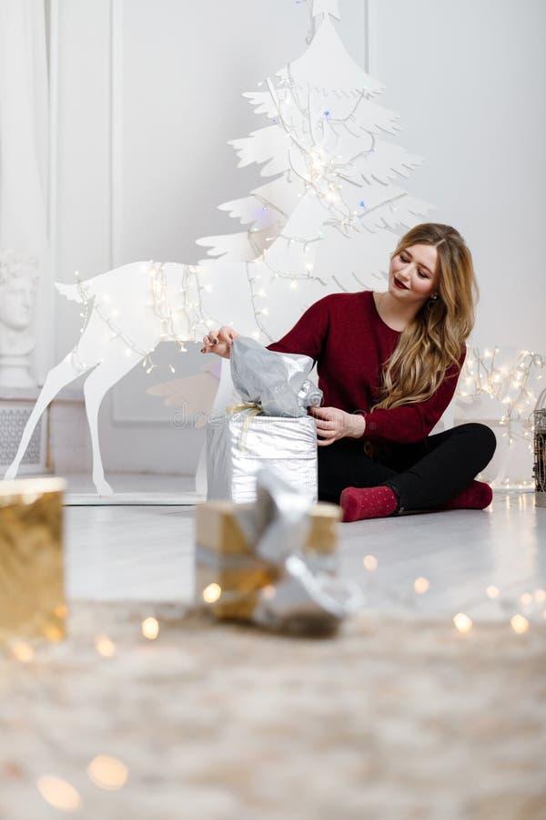 Szczęśliwa młoda dama z długie włosy prezentami grabą blisko choinki obrazy stock
