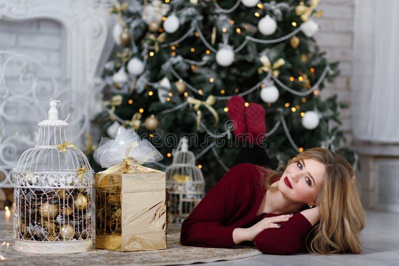 Szczęśliwa młoda dama z długie włosy prezentami grabą blisko choinki zdjęcia royalty free