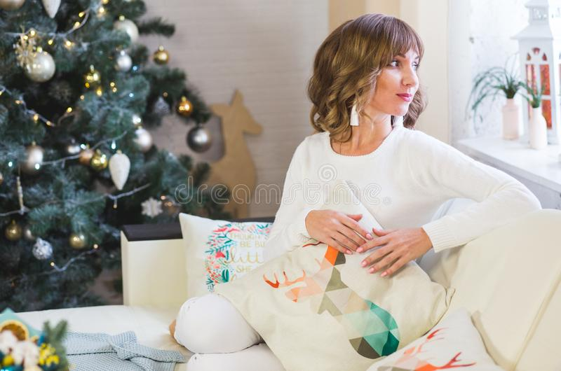 Szczęśliwa młoda dama z kędzierzawym włosy siedzi blisko choinki zdjęcia stock