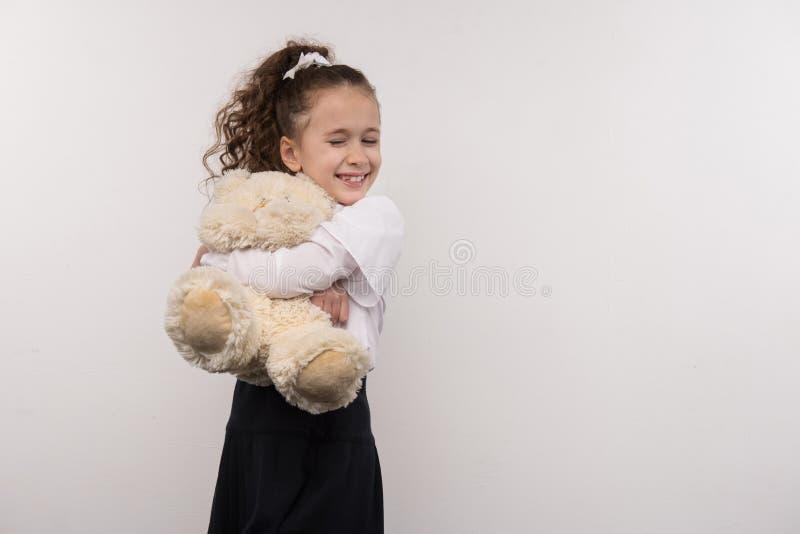 Szczęśliwa młoda dziewczyna ściska jej zabawkę zdjęcie stock