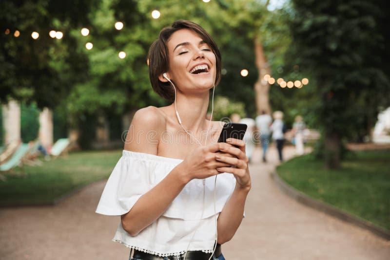 Szczęśliwa młoda dziewczyna słucha muzyka z słuchawkami fotografia stock