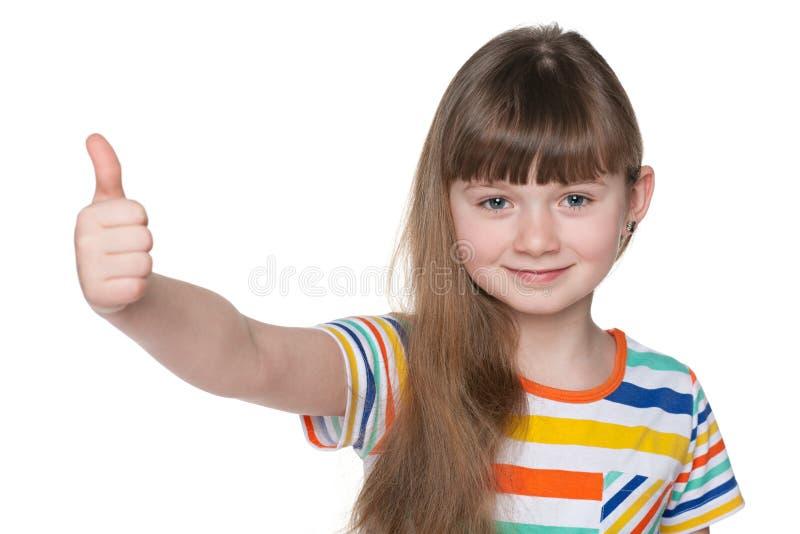 Szczęśliwa młoda dziewczyna trzyma jej aprobaty obrazy stock
