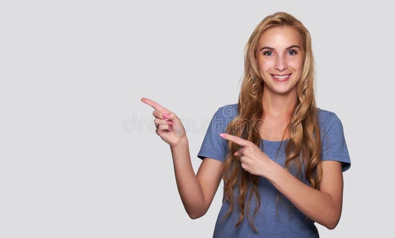 Szczęśliwa młoda dziewczyna wskazuje palec fotografia royalty free