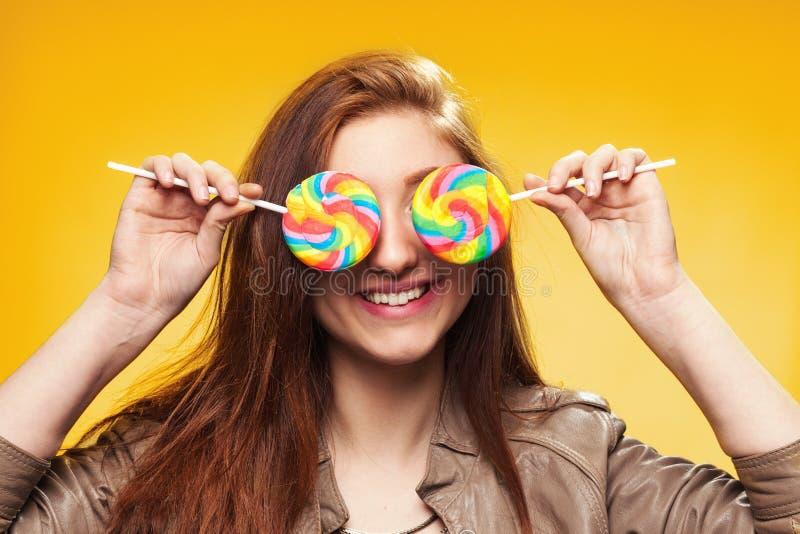 Szczęśliwa młoda dziewczyna z lizakiem na kolorze żółtym fotografia royalty free