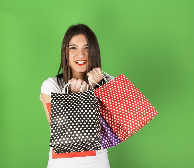 Szczęśliwa młoda dziewczyna z nierównymi torbami fotografia stock
