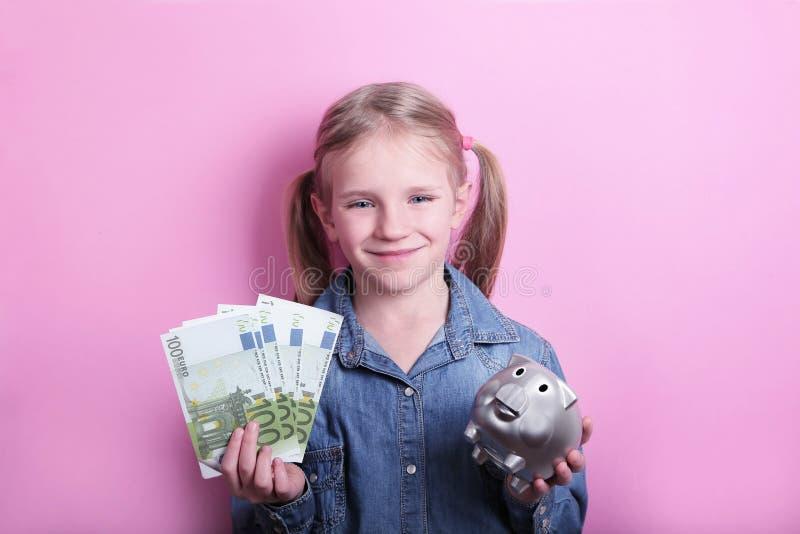 Szczęśliwa młoda dziewczyna z srebnymi prosiątko euro i banka banknotami na różowym tle koncepcja pieniędzy, żeby ratować fotografia royalty free