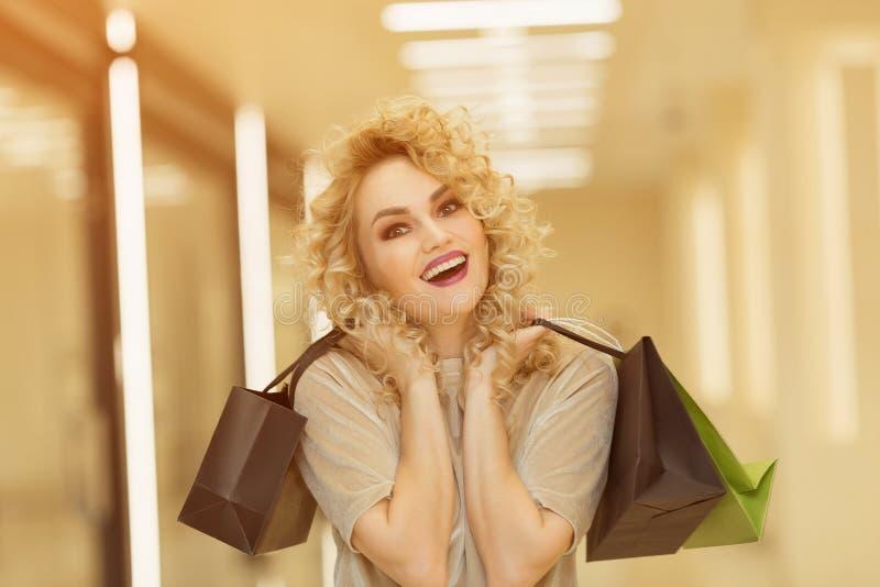 Szczęśliwa młoda dziewczyna z torba na zakupy w centrum handlowego ono uśmiecha się obrazy royalty free